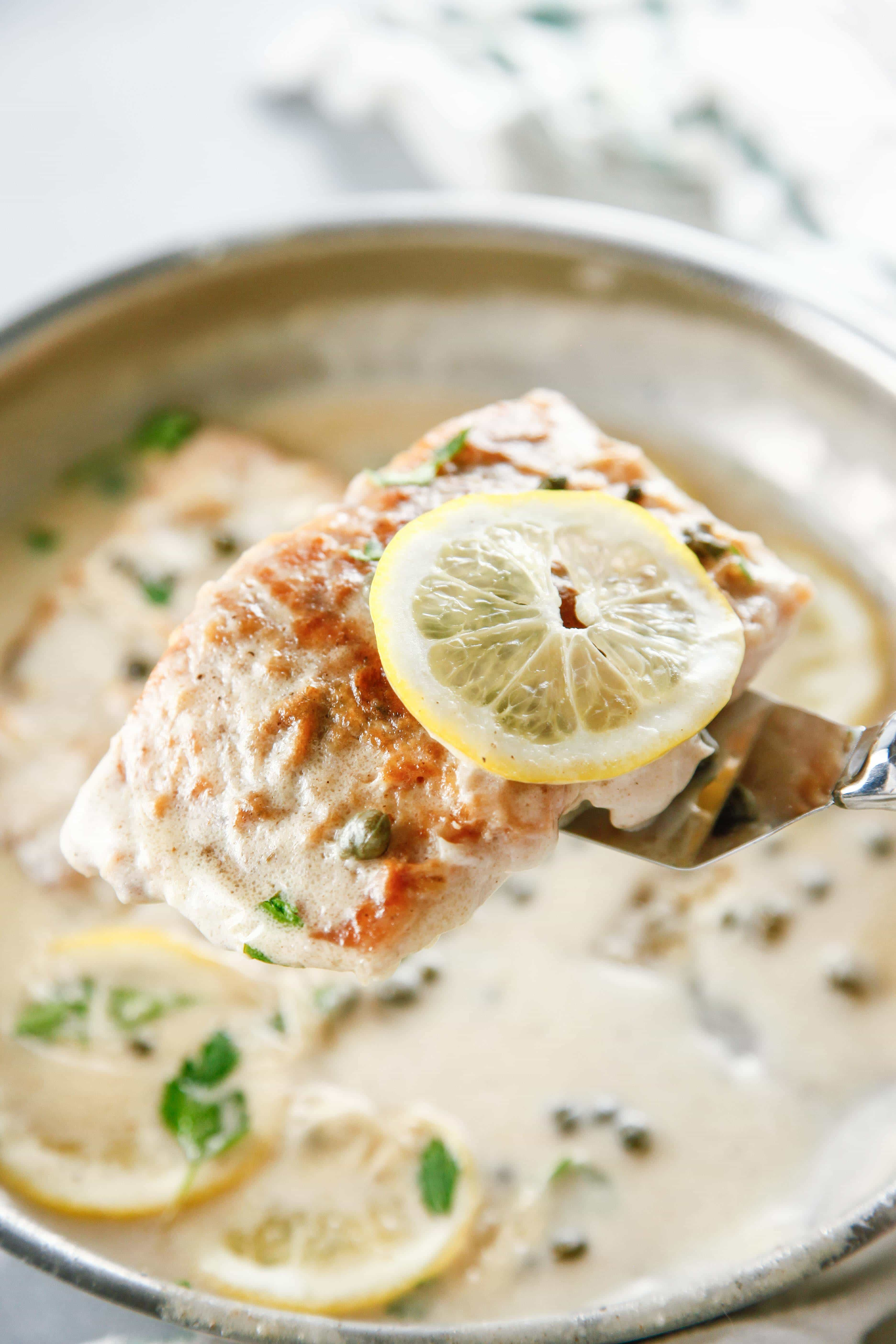 a closeup of a filet of Easy Salmon Piccata with a slice of lemon.